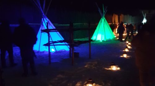 Tipis lit up in different colours along a path in Ste Marie amond the Hurons